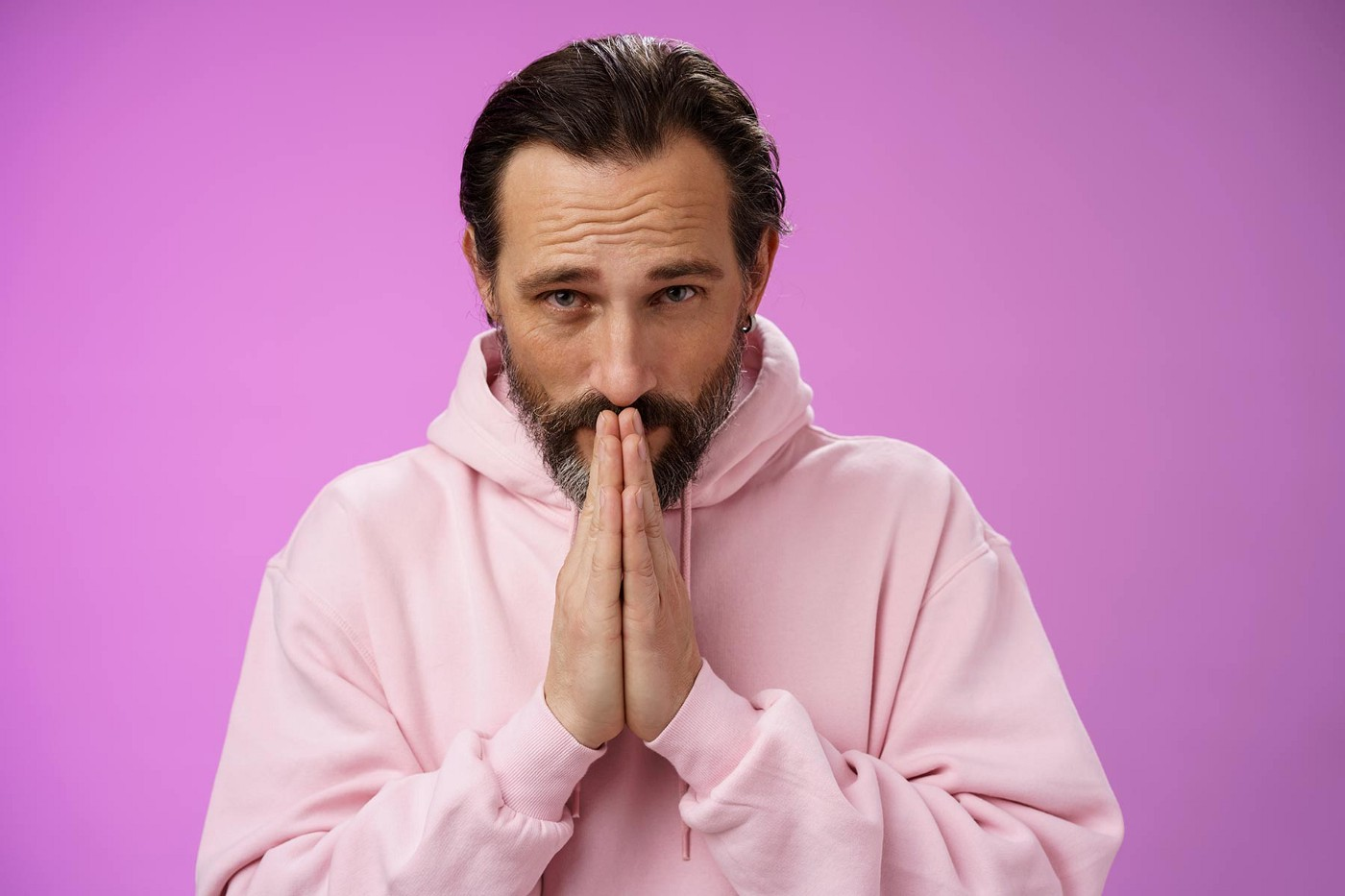 A middle-aged man wearing a pink sweatshirt says please with his hands up to his face.