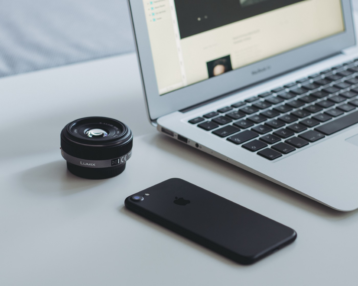 Computer, camera lens and cellphone, illustrating the routine of a freelance photographer.