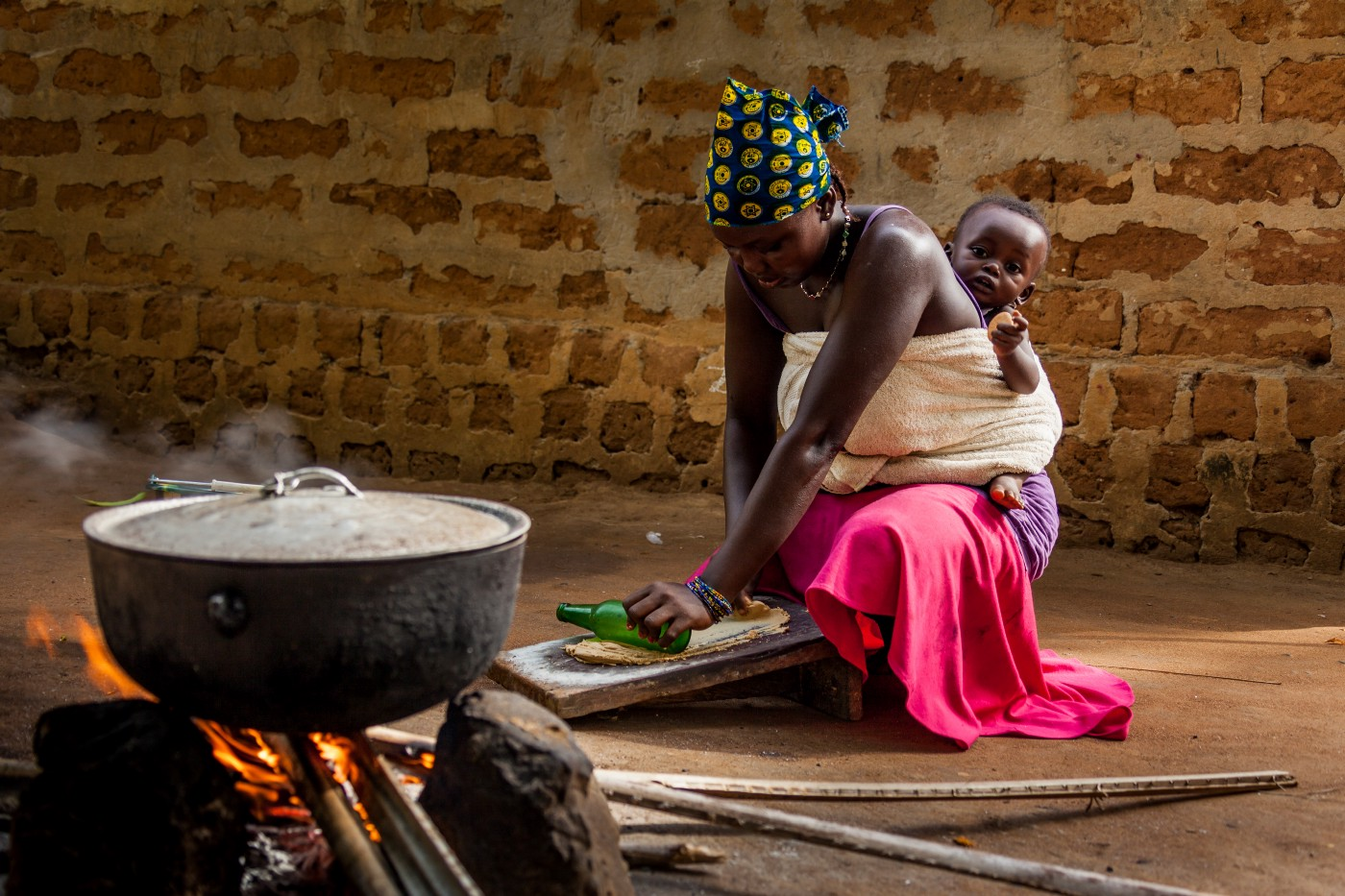 West African woman with a child on her back cooking over a fire.