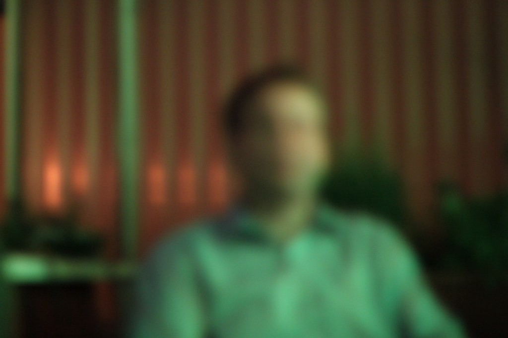 A blurred photo of a man in a presumed bar.