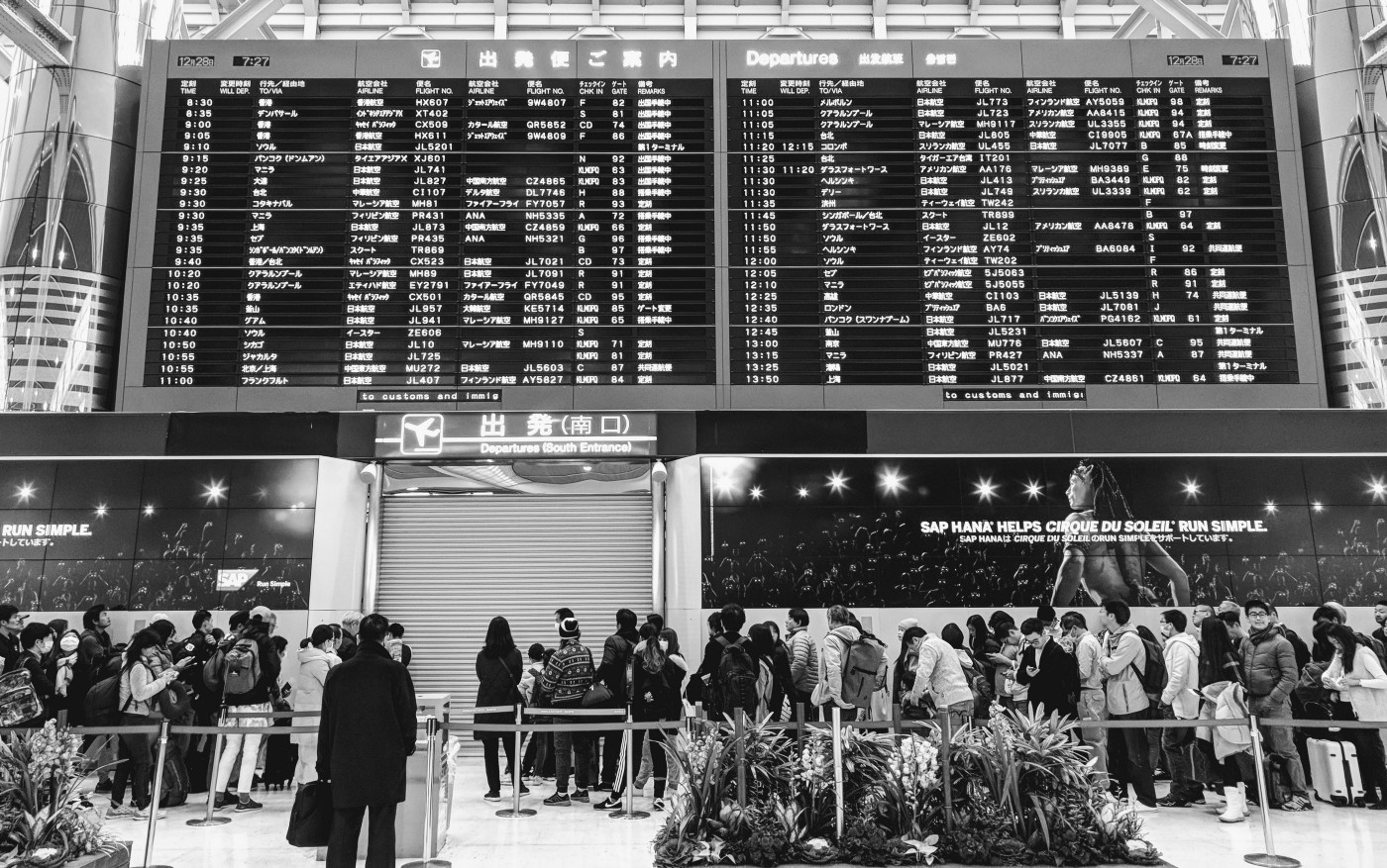 Black and white photo of airport terminal with departure screen.