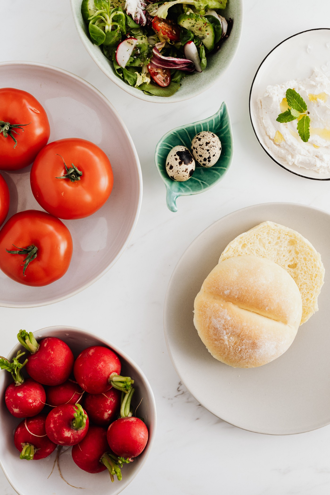 A table with vegetarian food- tomatoes, breads, etc