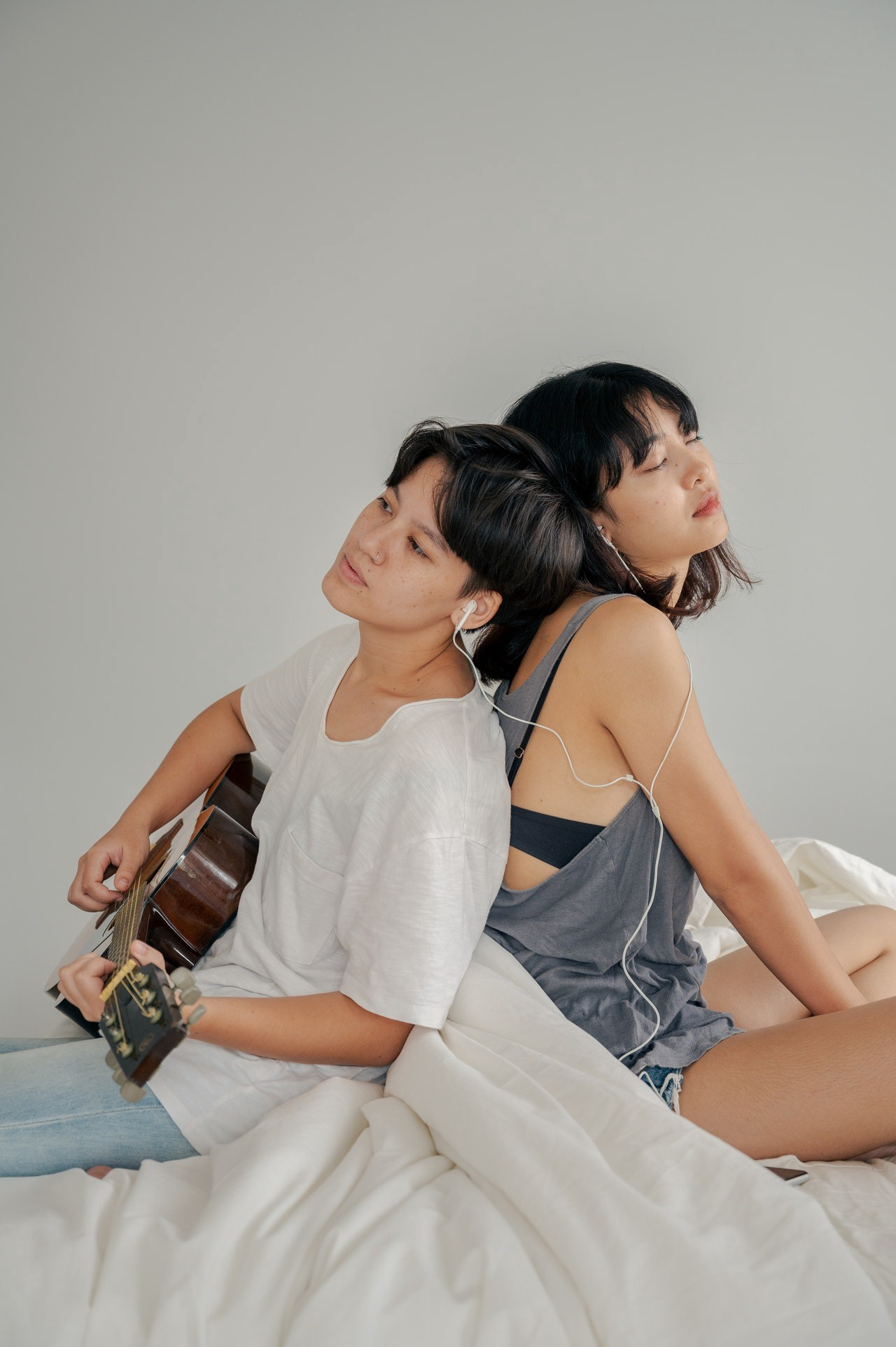 Picture of two women sitting on a bed, back to back, one of them with auriculars, the other playing guitar