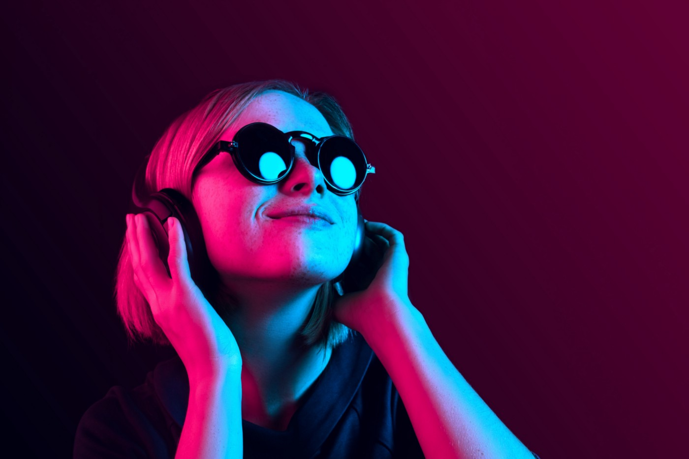 A photo of a girl with sunglasses and headphones on, with neon pink/blue lighting.