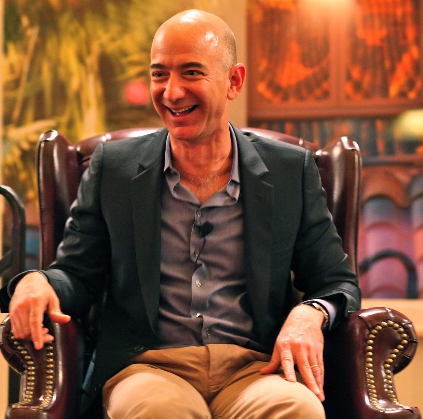 Jeff Bezos laughing while sitting in a leather chair