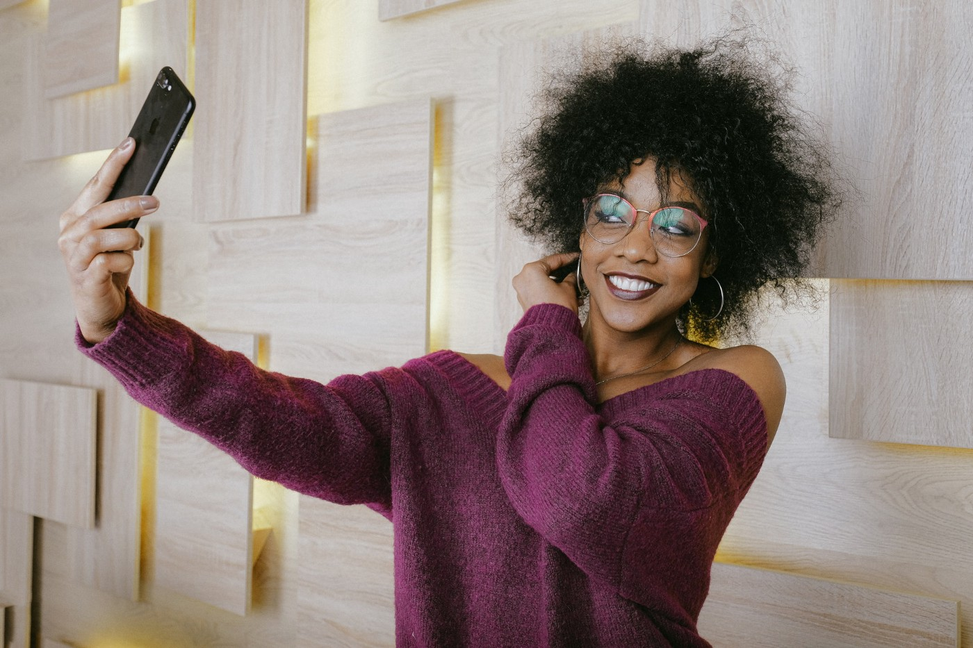 woman in purple shirt takes selfie with phone