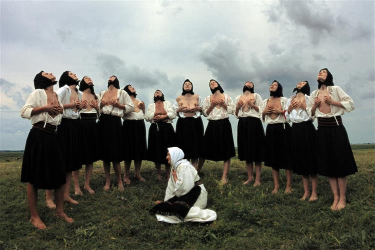Movie still showing semi-circle of Balkan women in traditional costume clutching their breasts.
