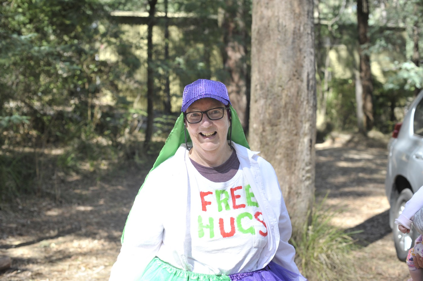 A woman in a purple sparkly hat and black-framed glasses smiles at the camera. She wears a white t-shirt that says FREE HUGS.