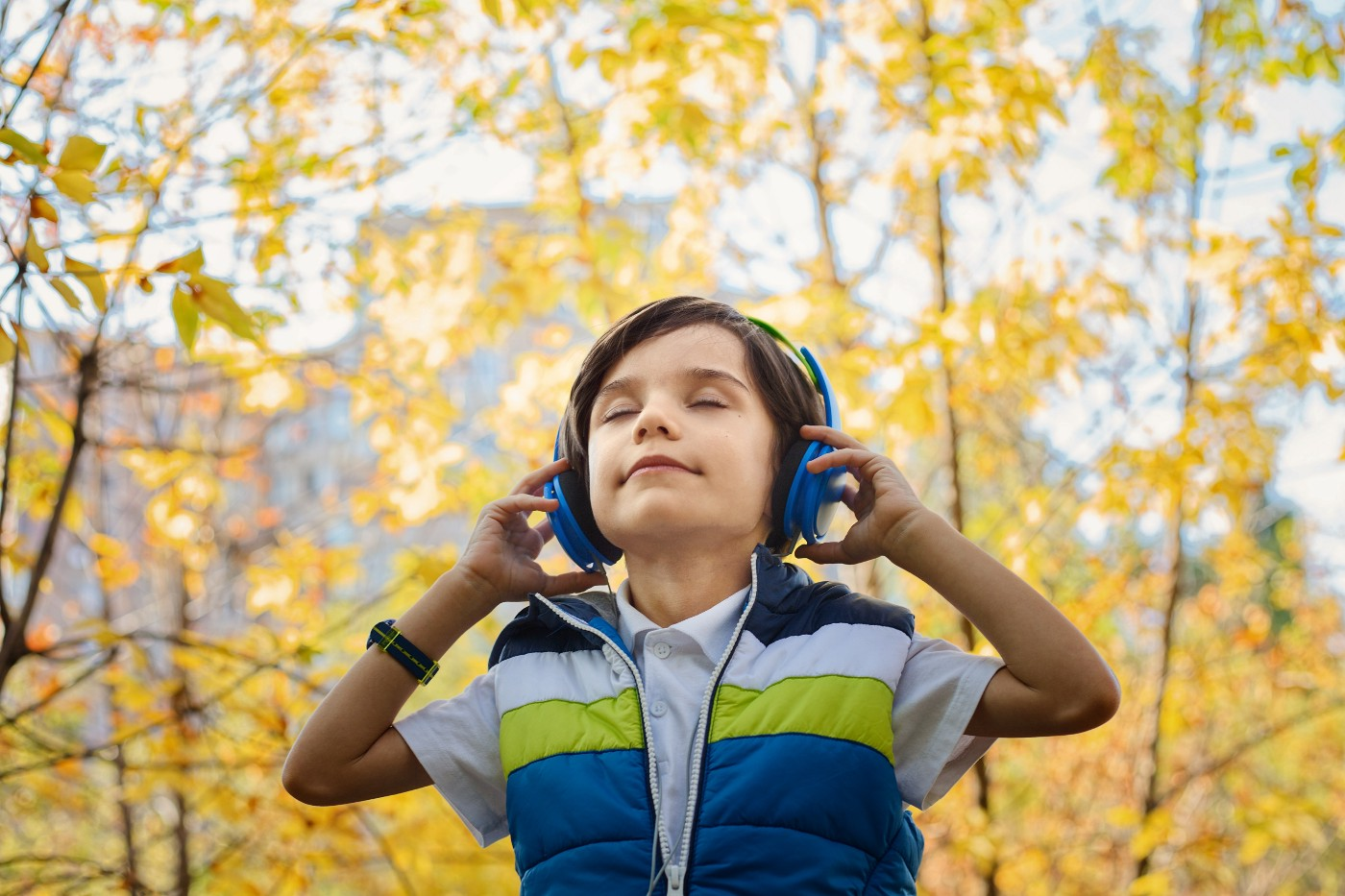 child listening to music through headphones with eyes closed