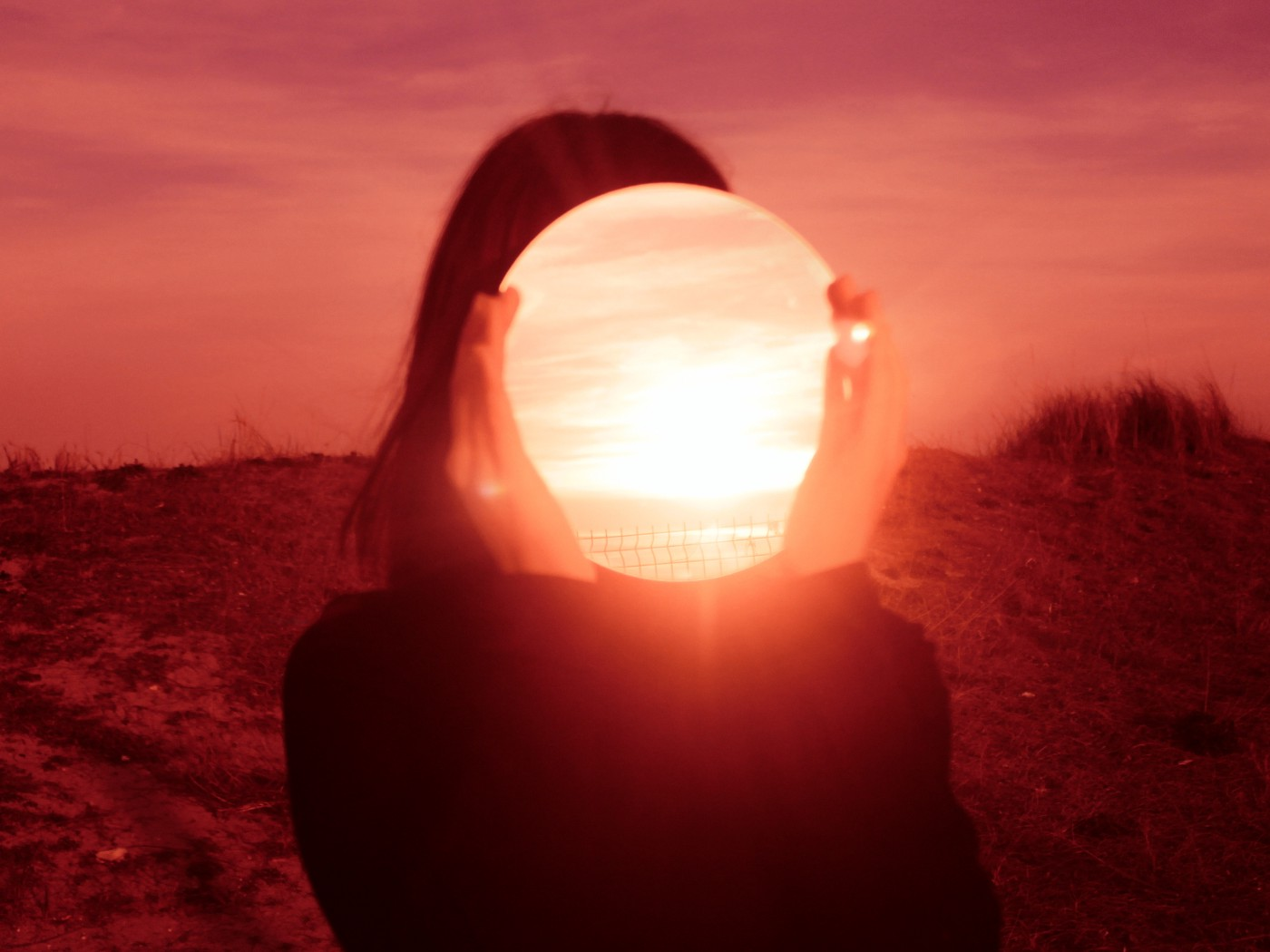 A woman holds a mirror over her face that reflects the bright light of the vivid red sunset.