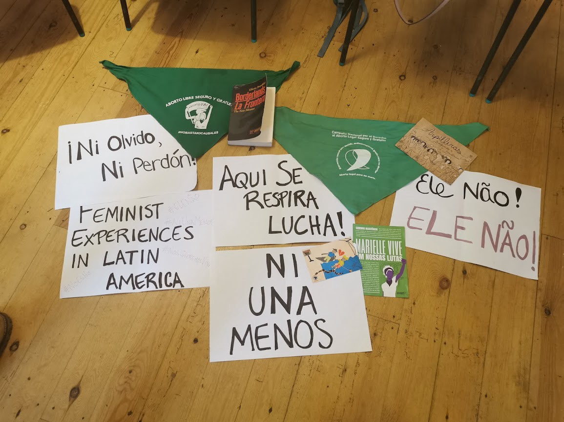 Photo of protest signs against violence against women on a wooden floor.