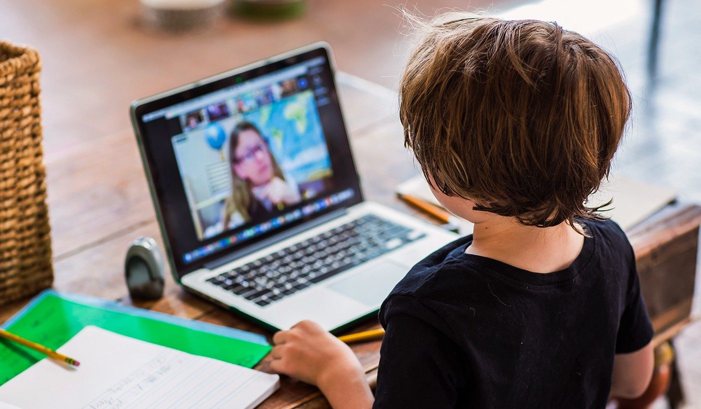 A grade-school child joins a virtual lesson with a teacher, pictured on the laptop screen.