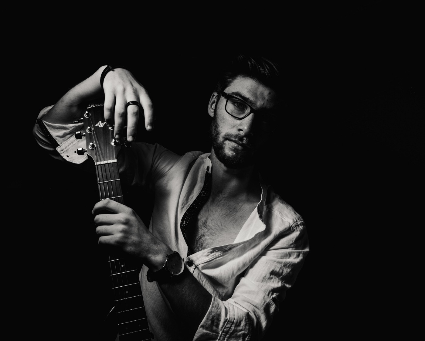A man with an unbuttoned shirt, glasses and a beard holds a guitar