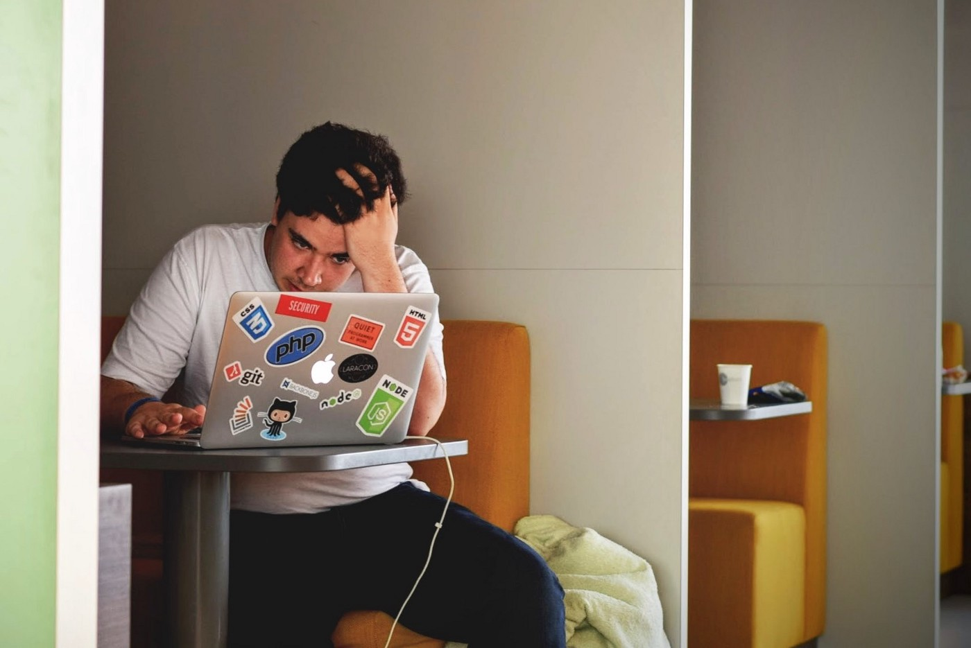 Developer looking at his laptop with hand in his hair