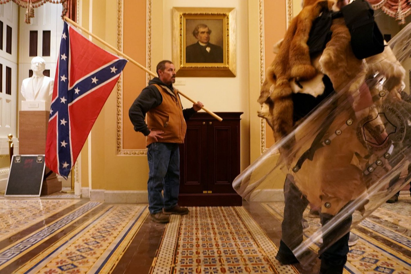 Man stands inside the U.S. Capitol with a confederate flag resting on his shoulder