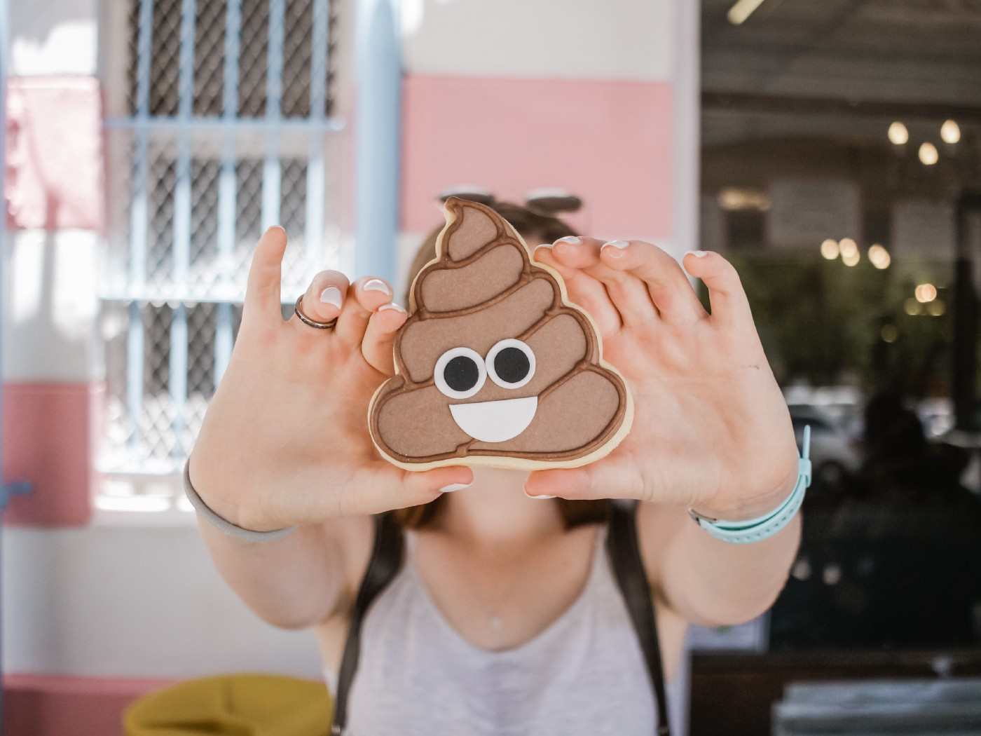 young caucasian girl holding poop emoji cookie  in front of her face with two hands. cookie has googly eyes and smily face.