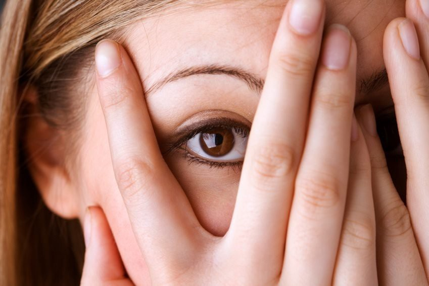 Person peeking out from hands covering face