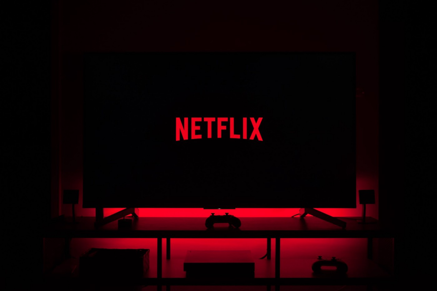 An image of the Netflix logo on a television screen in a dark room. The television is on top of a cabinet with a console gaming controller sitting in front of it. The red from the logo font resonates outward from the television giving a sort of ominous glow.