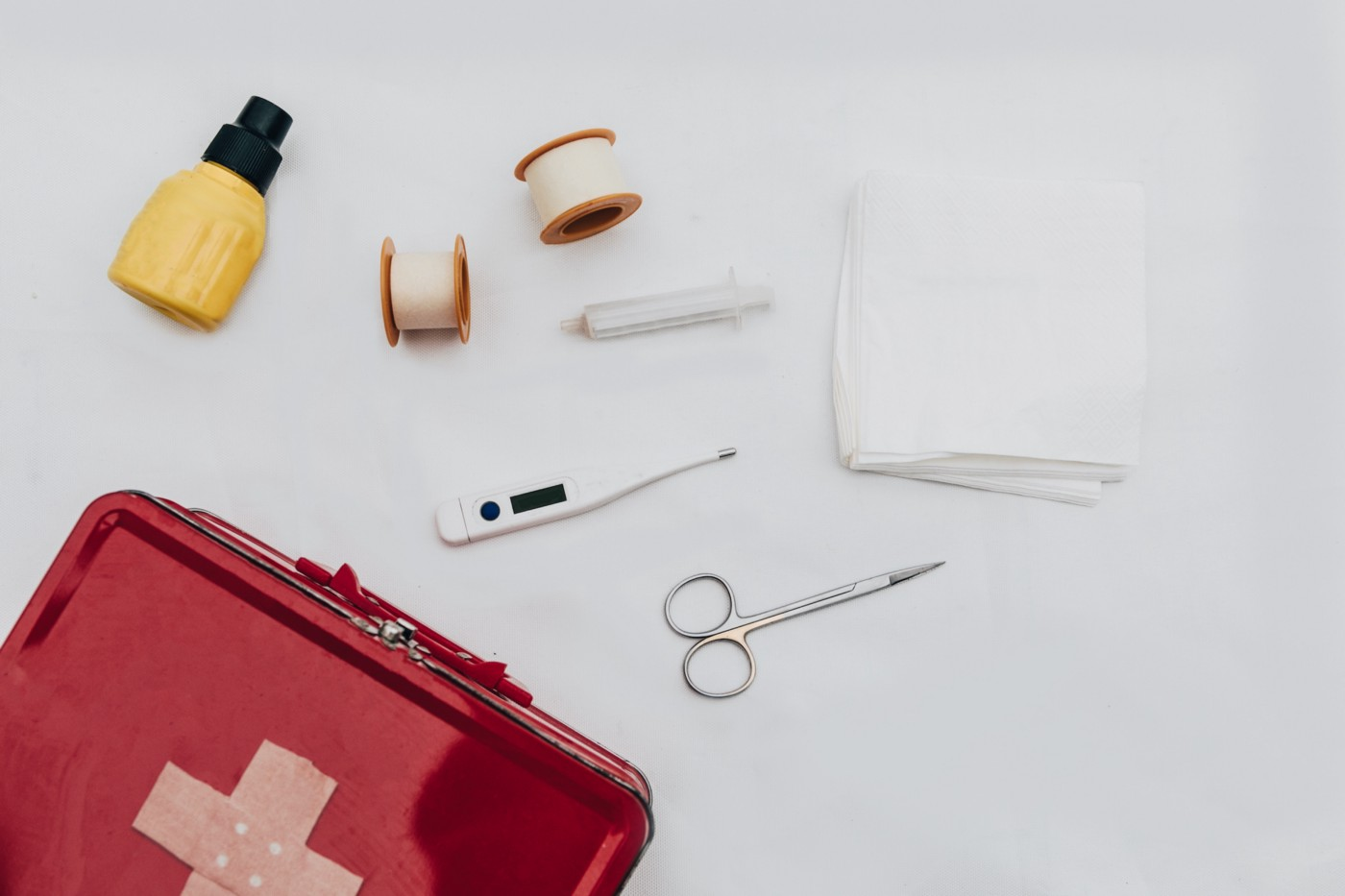 Overhead view of a red first aid kit and some of its contents: thermometer, scissors, gauze, and a small yellow bottle.