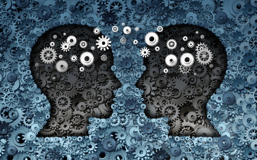 Silhouettes of two heads and the abstract representation of information transfer between them against a background made up of cog wheels and gears.