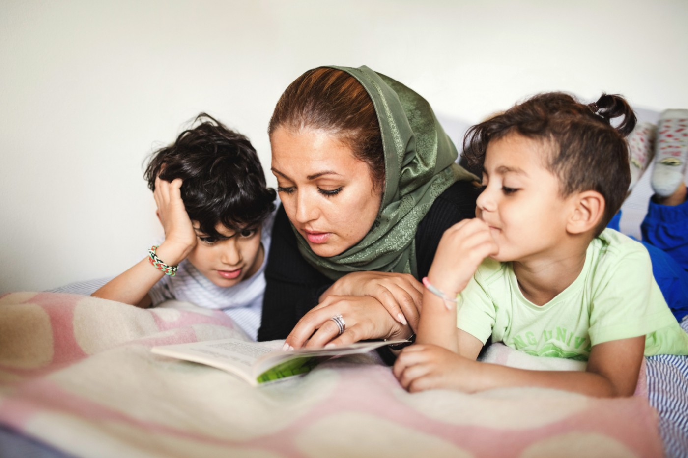 A photo of a Muslim mother reading a book to her two young boys.