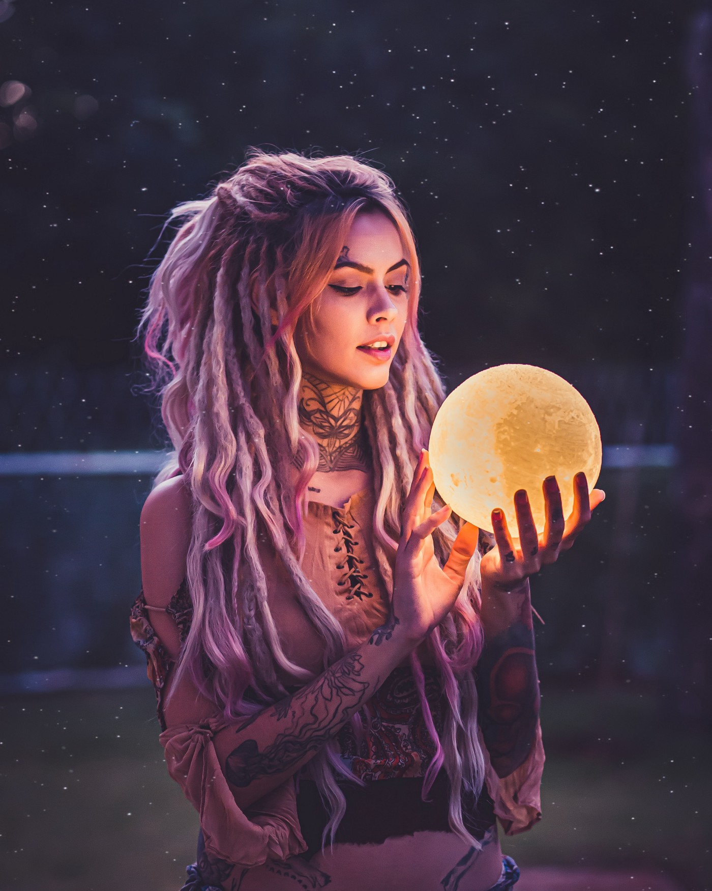 Woman holding full moon sphere emanating light, looking at it. It reflects light on her face. She has long dredlock hair and a design tattoo on her neck.