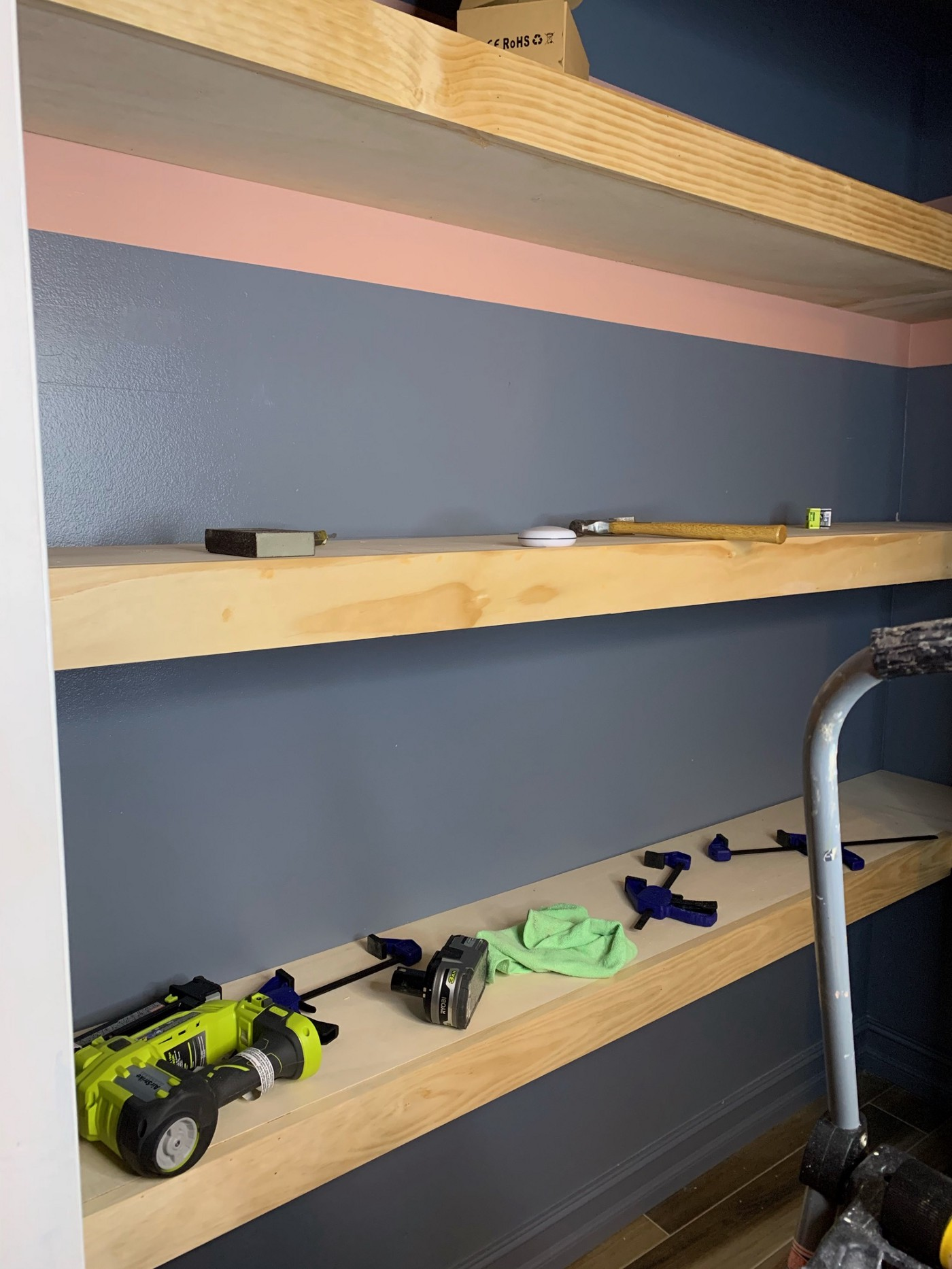 Inside the closet while it was being build. There are two shelves. The top shelf has a hammer on it and some misc objects. The lower shelf has clamps, a Ryobi brad nailer and a battery. The wall is a blue/gray with the top part of the wall painted pink. The floor is a wood look tile.