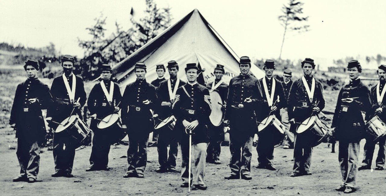 Black and white photograph of 14 men in Union uniforms standing outside a tent. Most carry drums, some carry fifes. The man standing front and center holds a sword in front of him with the point on the ground. Two of the drummers appear to be black; the remainder of the men appear to be white.
