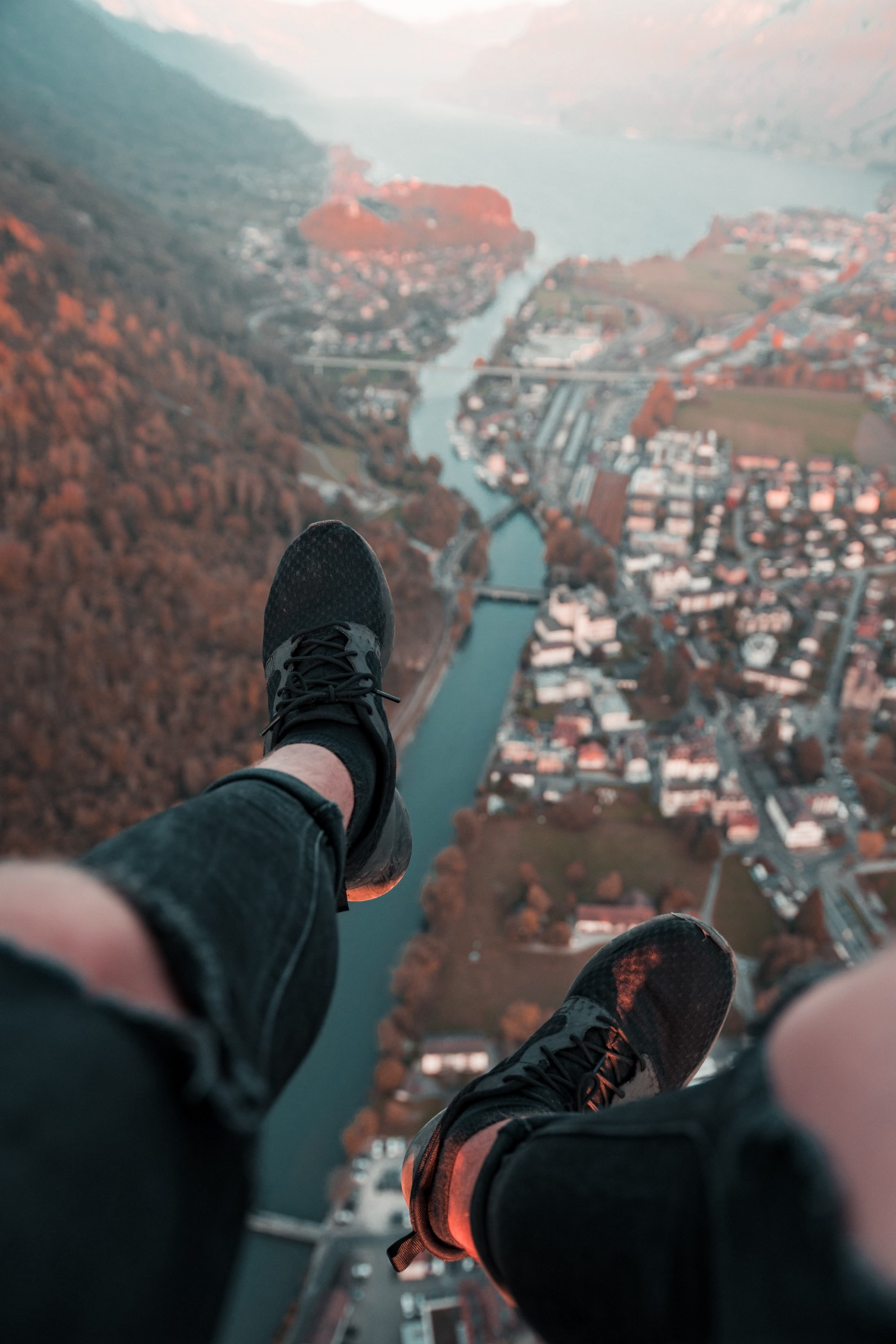 Man dangles feet over cliff looking down onto a city