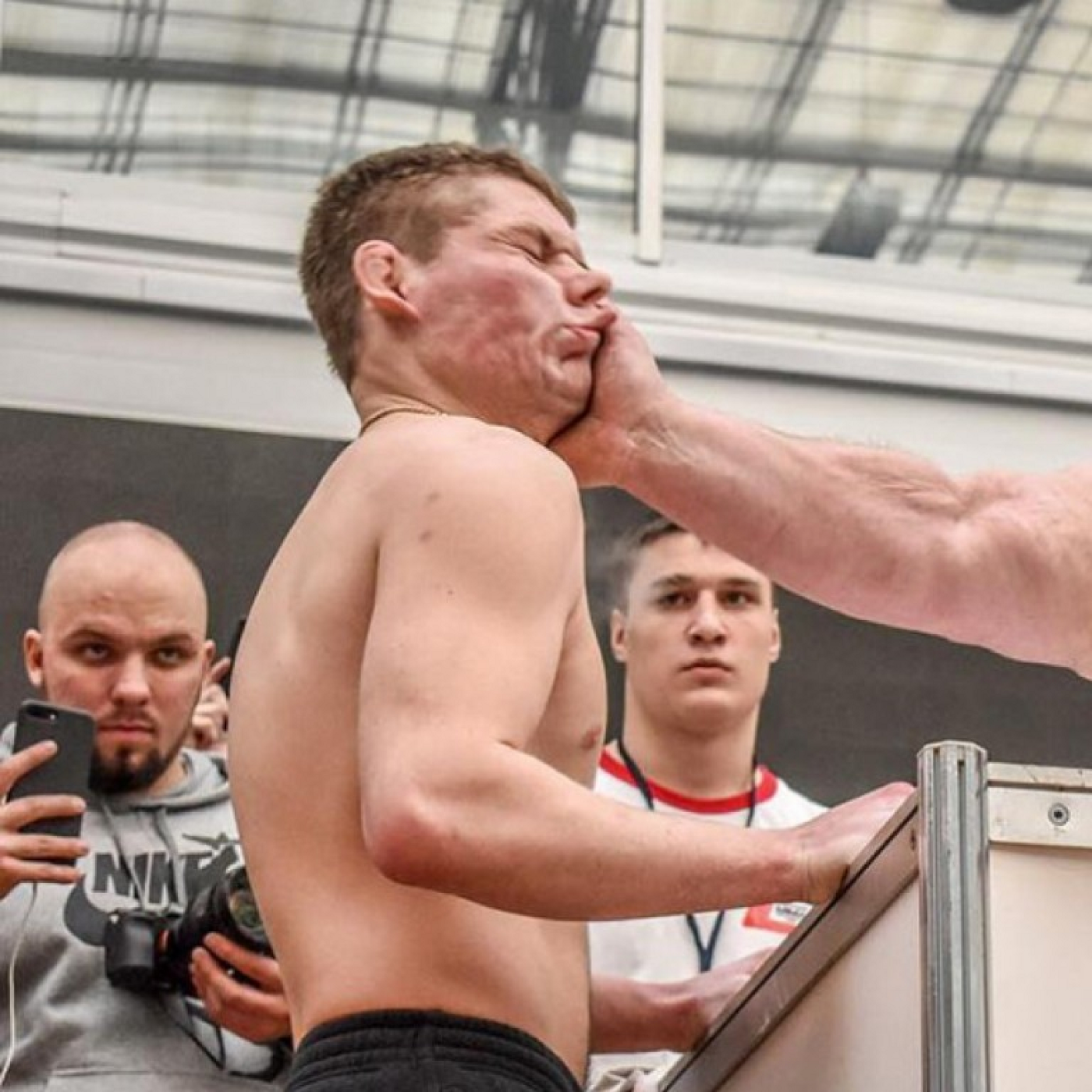 Man taking a big hit at a slapping competition.