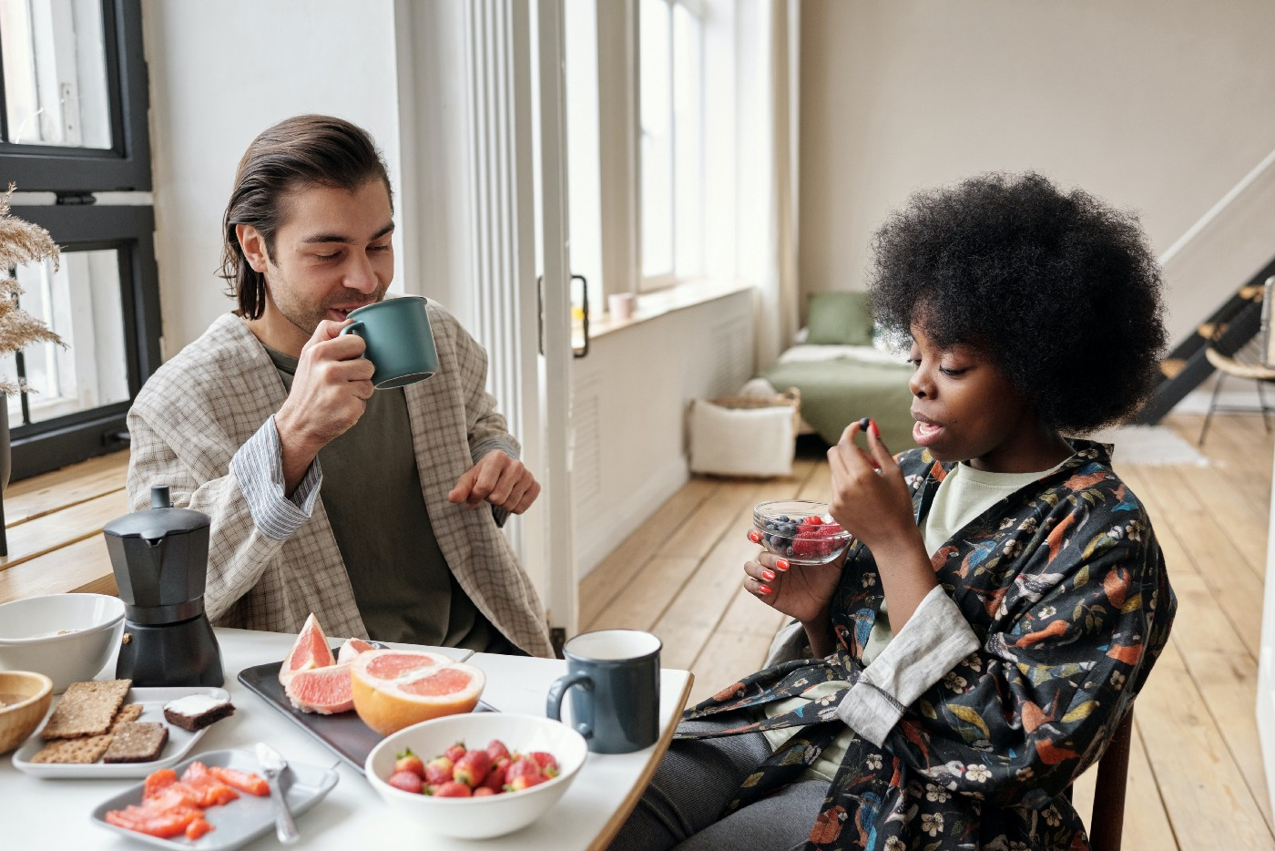 Man and a woman at a table eating breakfast