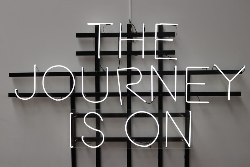A neon sign that reads the journey is on