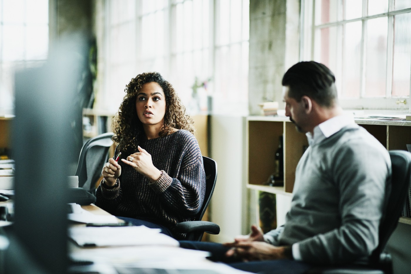 A woman discusses her idea in a meeting with a male colleague.