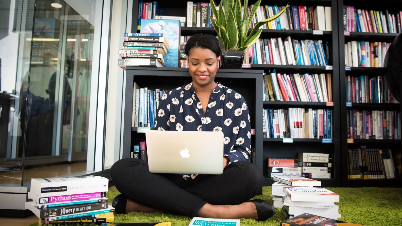A woman sits cross legged on the floor of a library with a Mac laptop surrounded by technical books.