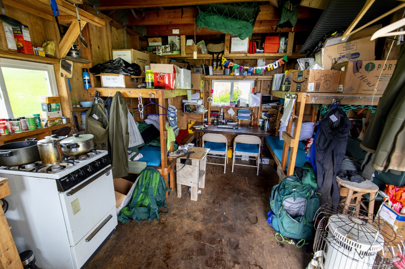 Interior of a small one room cabin showing a stove and oven, two wooden bunks, a table and two chairs near a window, backpacks, and many boxes, supplies, and gear.