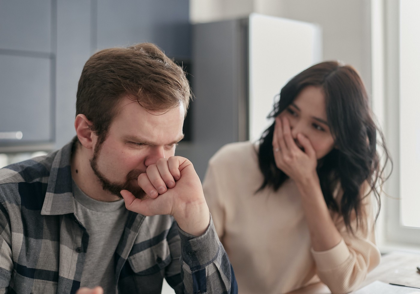 frowning man and woman with a hand over her mouth in shock