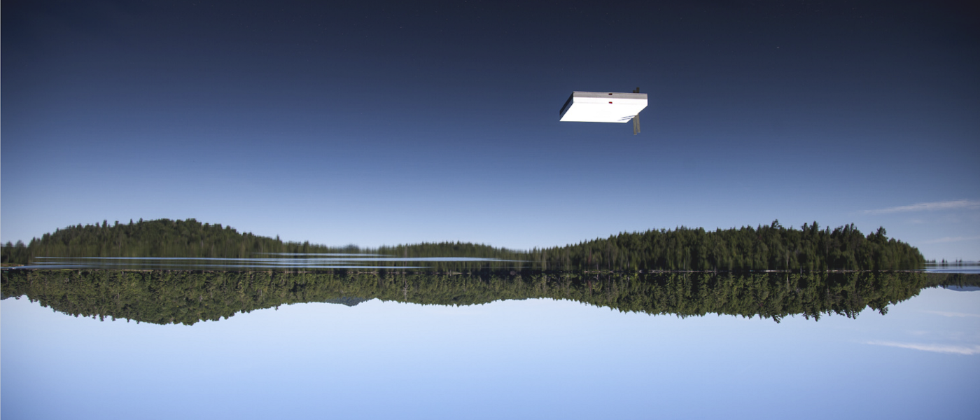 Upside-down image of a blue lake above a blue sky with a white raft seeming to hover in the sky.