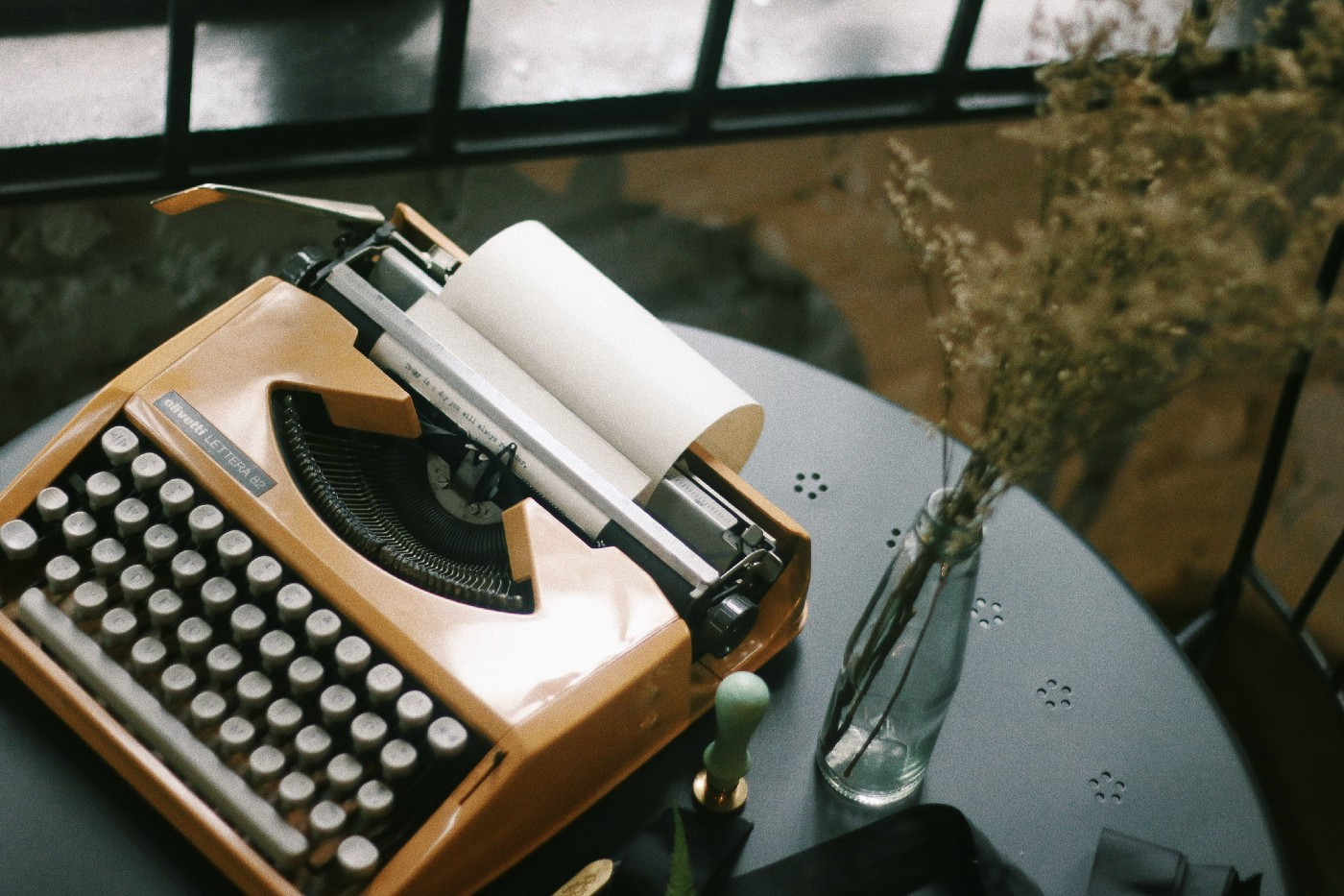 typewriter on table with vase of dried flowers