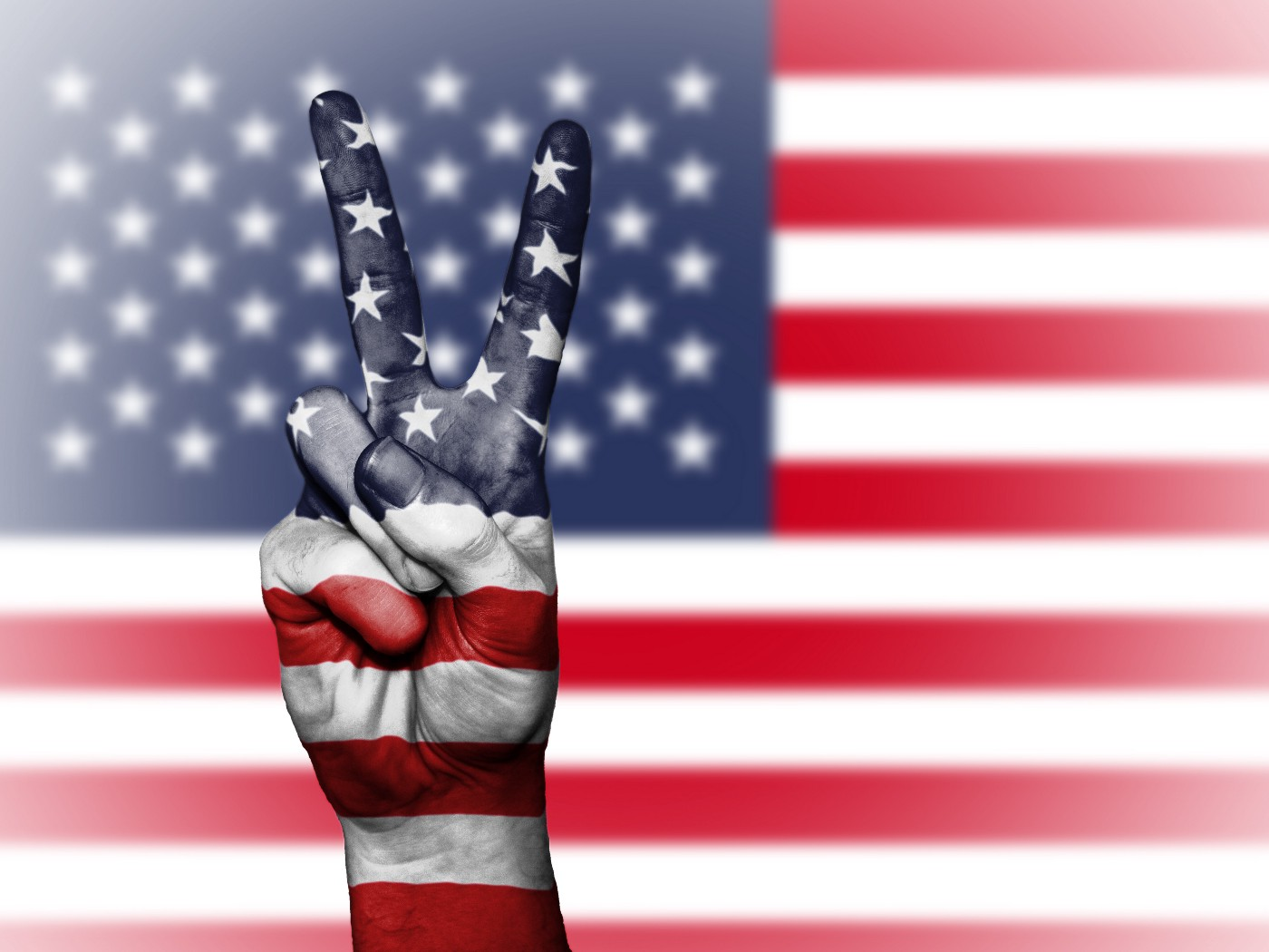 A hand holding up a peace sign with an American Flag image laid over it