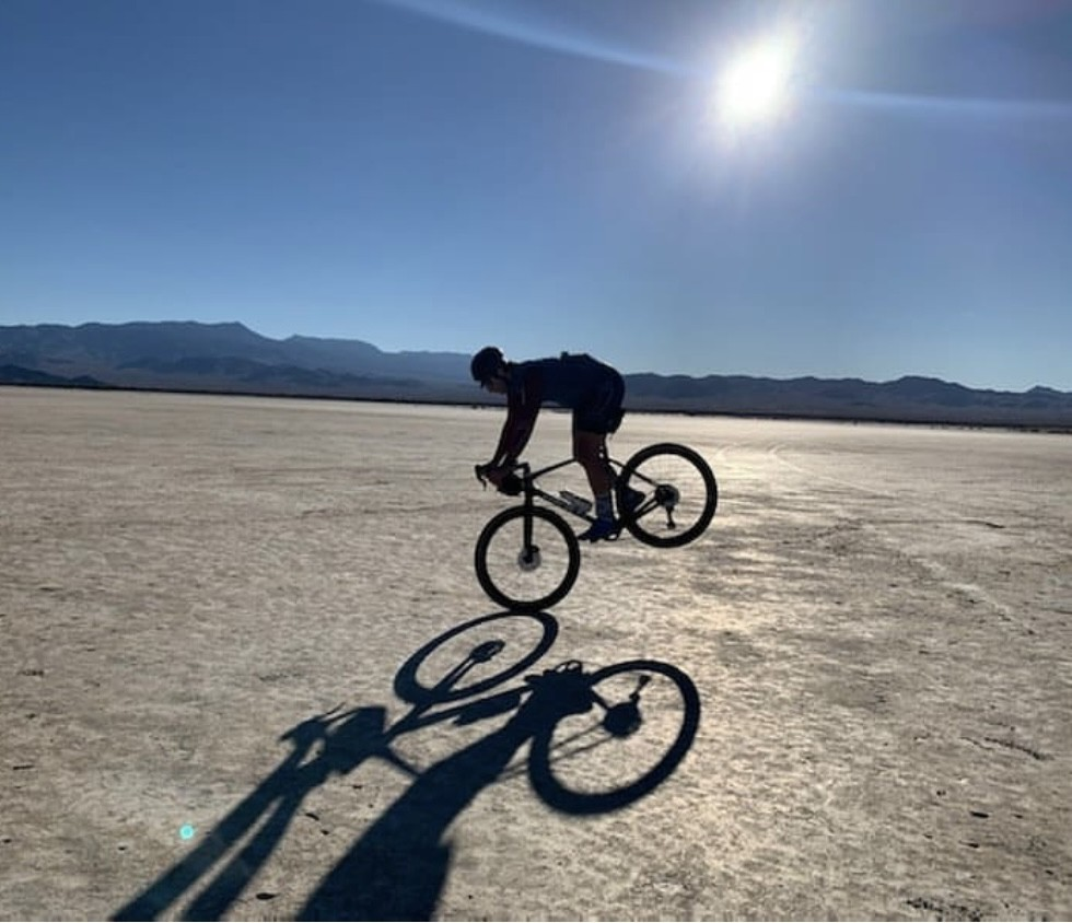 a guy pops a reverse wheeley on his bike in the desert
