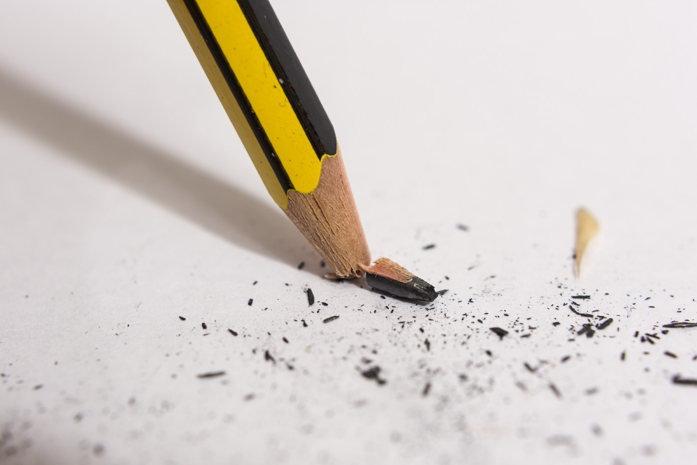 A yellow and black pencil is pressed against paper and the tip of it has just snapped under the pressure.