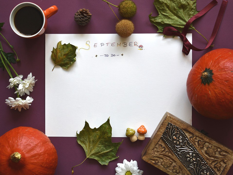 """A picture of a sheet of paper with """"September"""" written on it, surrounded by pumpkins and leaves, indicating fall season"""