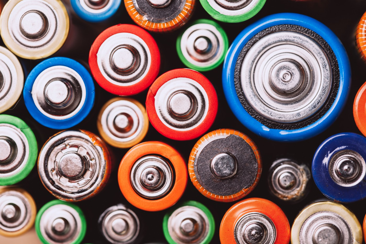 A stack of all different sizes and types of batteries, displayed with their cathodes facing forward