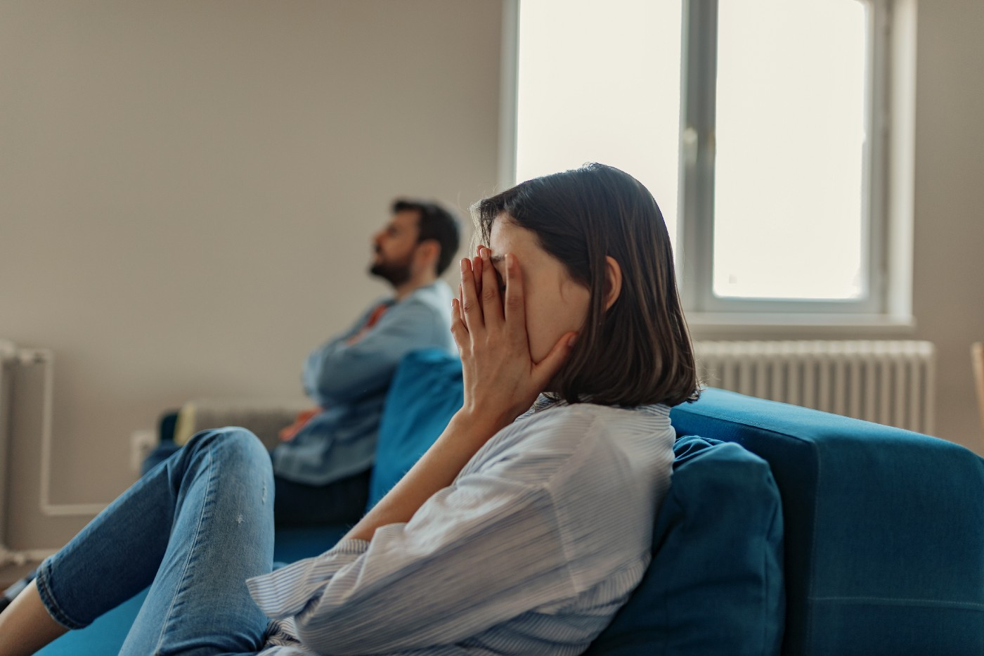 Unhappy couple sitting at the ends of a sofa.