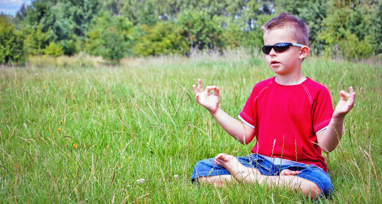 Small boy wearing sunglasses sitting in the lotus position in a field