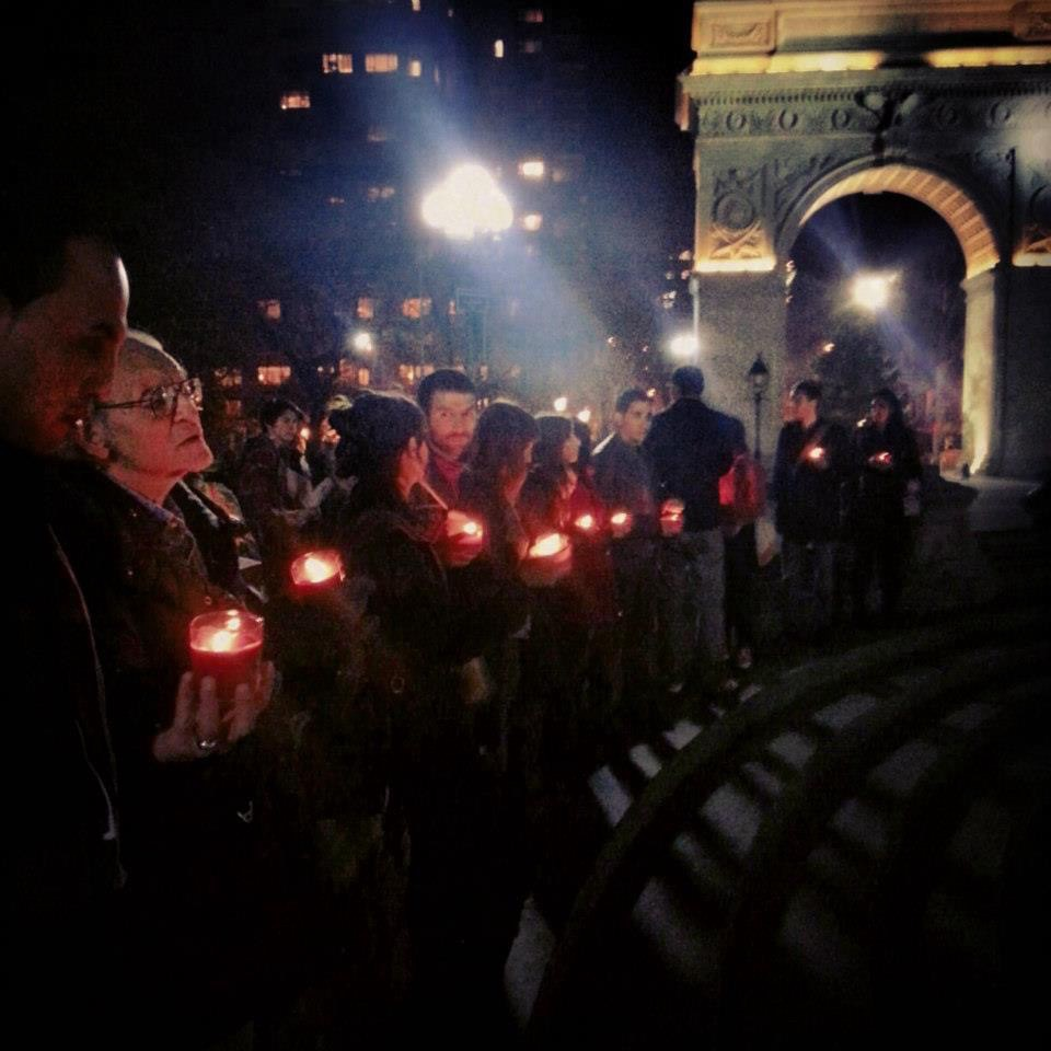 Students and faculty in front of the arch at Washington Square Park at night, holding candles.