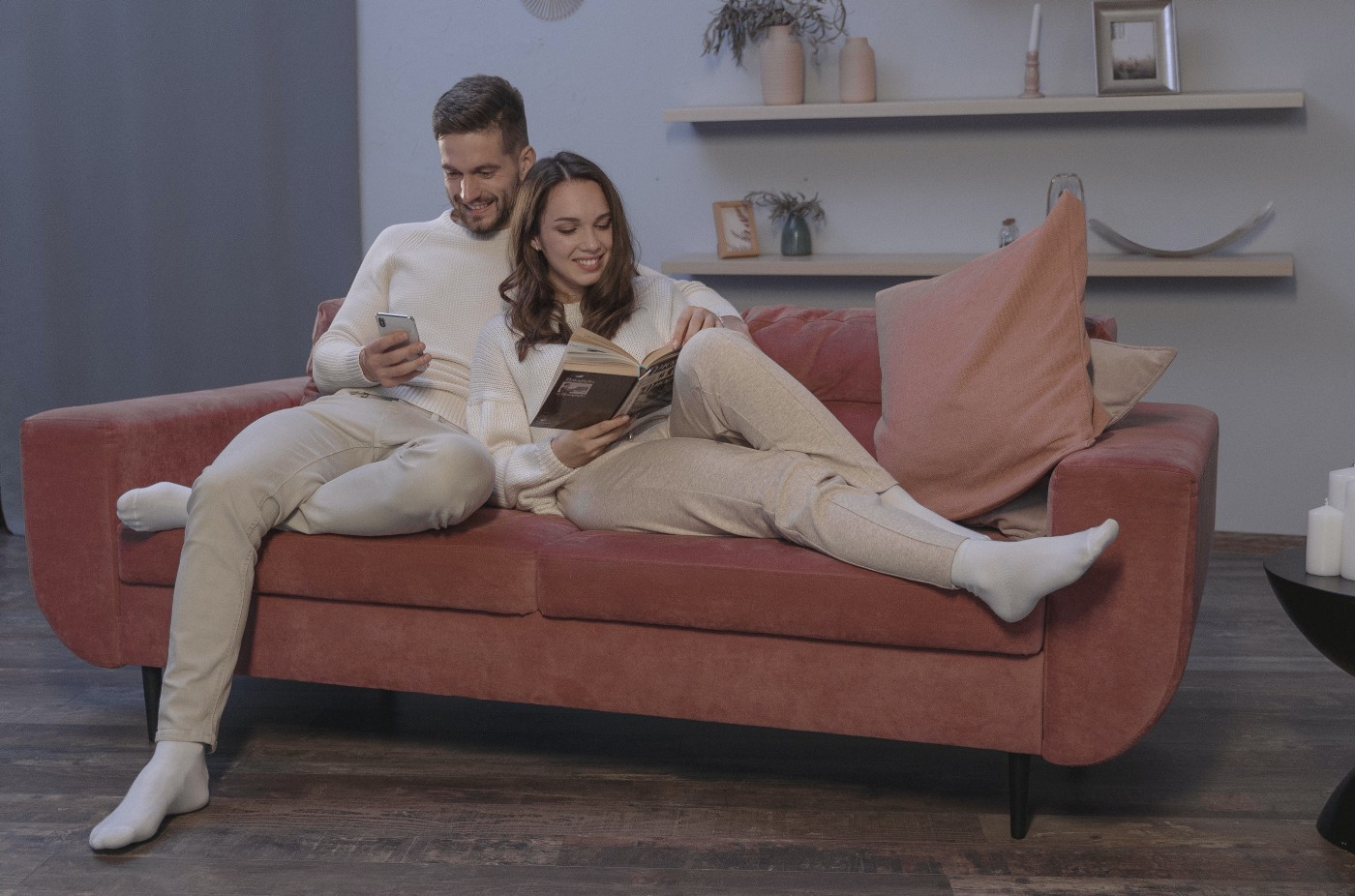 A Happy heterosexual Couple Sitting on a Couch. The man is on his smart phone and the woman is reading a book.
