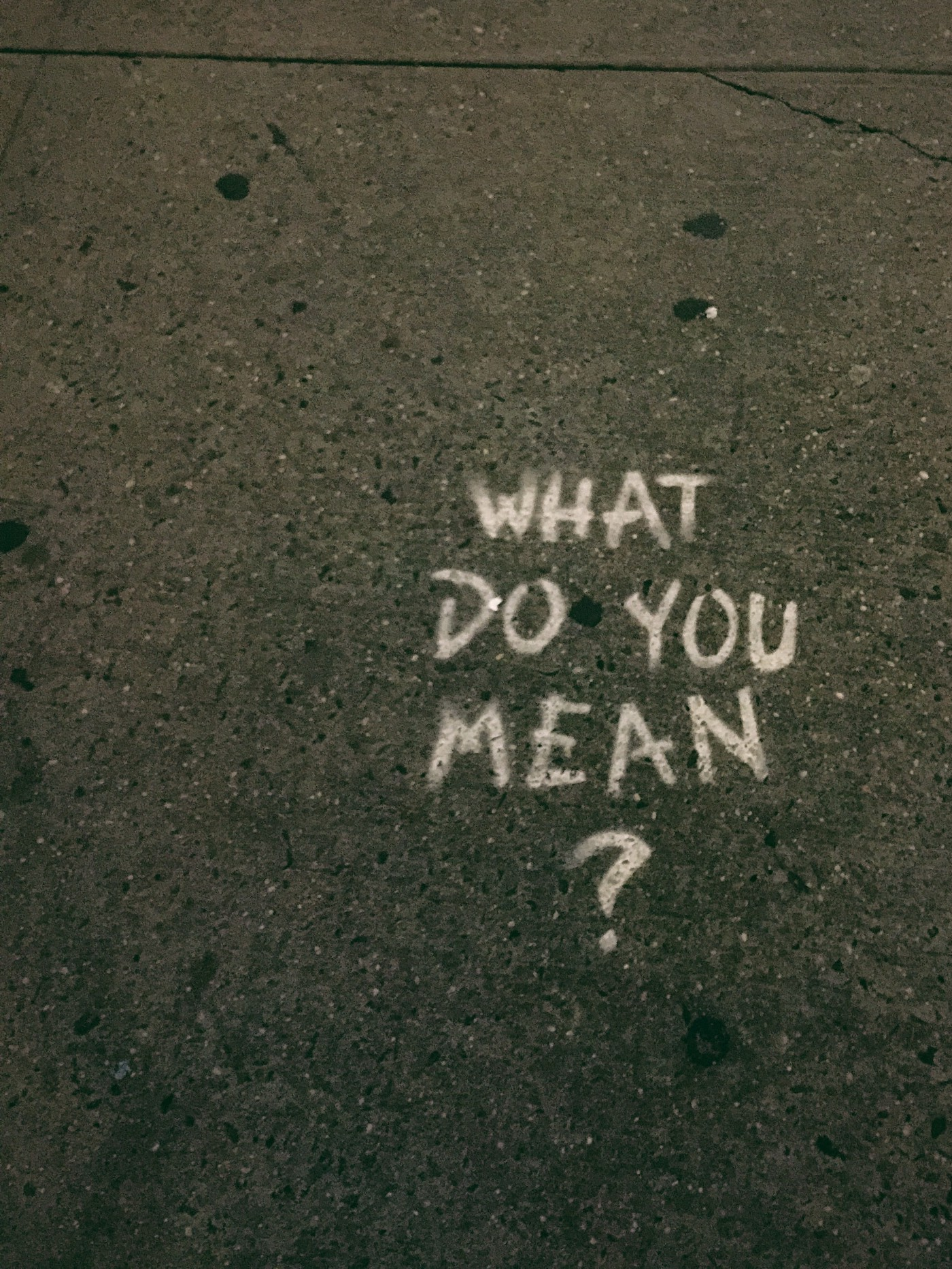 "The words ""what do you mean?"" spray painted onto a road."