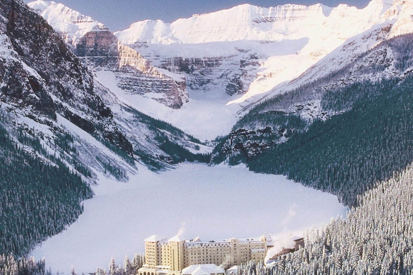 A hotel in a snowy valley with snow-covered evergreen trees in the foreground and snowy mountains in the background.