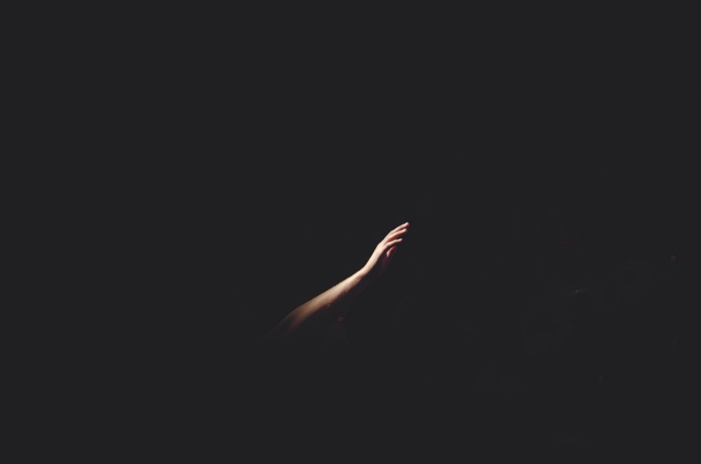 A person reaches out in the dark. Looking for success.